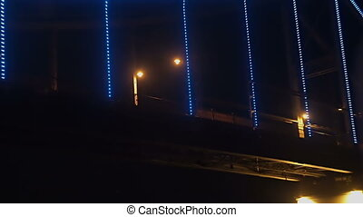 Sailing under the night illuminated bridge