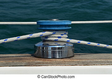 Sailboat on the lake with main sail sheet line wrapped tightly around winch