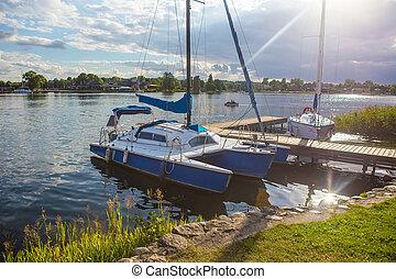 sailing yacht and catamaran moored on the lake