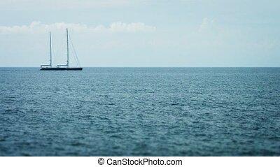 Sailing Yacht Cruises under Motor Power on Tropical Sea....