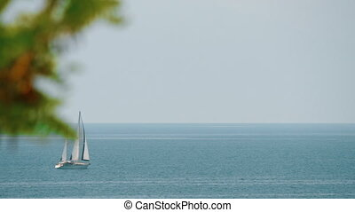 Sailing yacht in quiet blue sea - View to the yacht sailing...