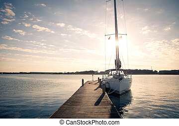 Sailing yacht moored to the pier at sunset