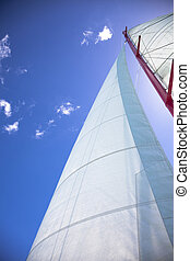 Sailing - yacht sail and blue cloudless sky above