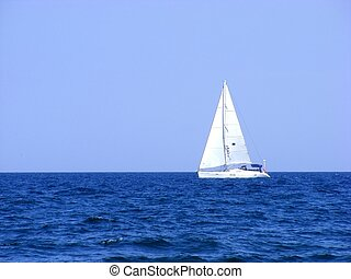 Sailing yacht with triangular sails of white sails on the...