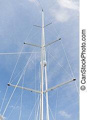 close up of sailboat mast over blue sky