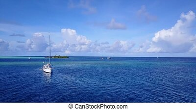 sailing yachts and boats with view from aerial flying drone in clear aqua blue sea water and blue sky