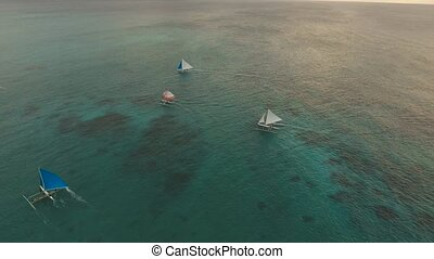 Sailing yachts at sunset - aerial footage sailboats with...