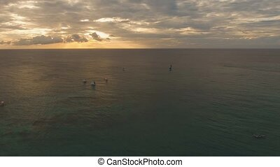 Sailing yachts at sunset - aerial footage sailboats with...