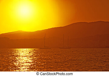 Sailing yachts in golden haze at sunset