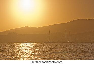 Sailing yachts in golden haze