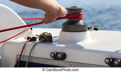 Sailor and winch on yacht