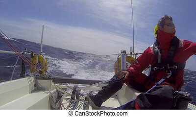 Single handed sailor steering his boat through at hight speed, during a race over the Atlantic Ocean