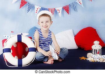 Sailor boy sitting with stearing wheel in marine decor