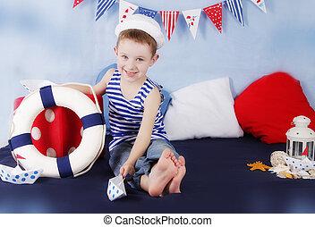 Sailor boy sitting with steering wheel in marine decor