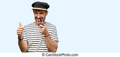 Sailor captain man smoking a tobacco pipe smiling broadly showing thumbs up gesture to camera, expression of like and approval isolated over blue background