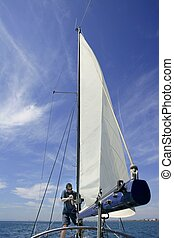 Sailor in sailboat rigging the sails over sunny summer blue...