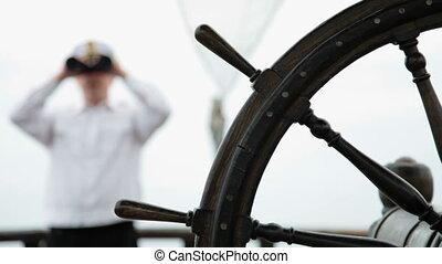 Sailor looking through binoculars - old wooden ship wheel in...