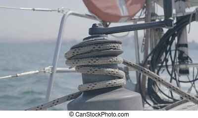 Sailor man using sail winch and rope while sailing on yacht in sea close up