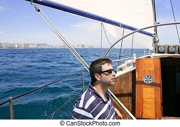 Sailor sailing blue tropical sea on sailboat