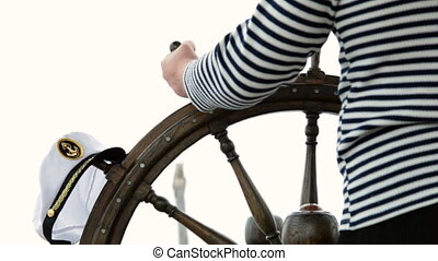 Sailor turns steering wheel - sailor in a striped shirt...