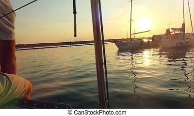Sailor with paddle surf in slowmotion  at the amazing sunset over the sea on a yacht
