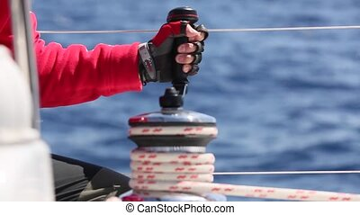 Sailor's hand on a winch of sailing