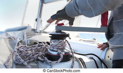 Sailor's hand on a winch of yacht