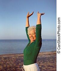 sain, femme aînée, pratiquer, yoga, sur, plage