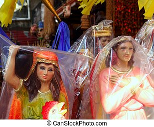 saint and virgin figurines in mexican market