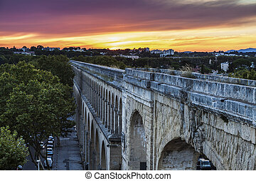 Saint Clement Aqueduct in Montpellier at sunset. Montpellier...