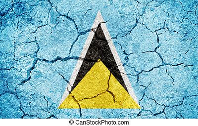 Saint Lucia flag on dry earth ground texture background