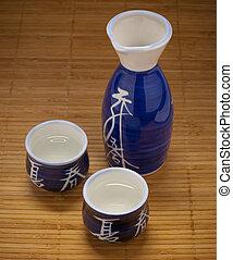 Sake flask and cups on bamboo - A sake flask and two ...