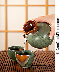 Sake for two - Hand pouring sake in a traditional japanese ...