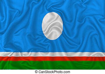 Sakha Republic flag on wavy silk textile fabric background.