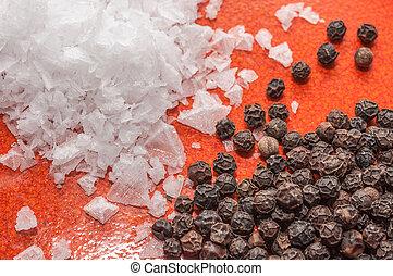 Plato naranja con escamas de sal y pimienta negra en grano