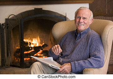sala, sentado, periódico, sonriente, chimenea, hombre