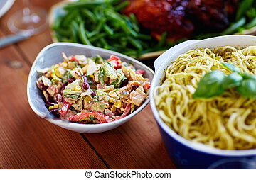 salad and pasta in bowls with other food on table