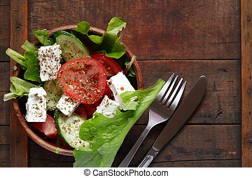 Bowl full of freshness salad with feta cheese on wooden table