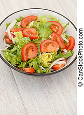 Salad bowl on a white wooden background