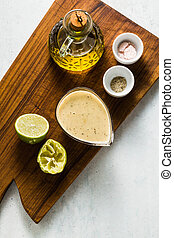 salad dressing of olive oil and lemon juice or lime with seasonings on a cutting wooden board. classic vinaigrette
