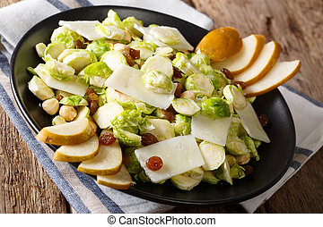 salad from Brussels sprouts with nuts, cheese, raisins and fresh pears closeup. horizontal