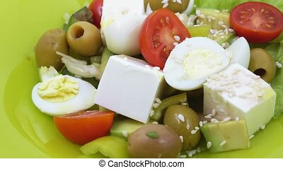 Salad from greens on plate - Salad of olives, avocado, sweet...