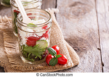 Salad in mason jars - salad with tomatoes, green leafs and...