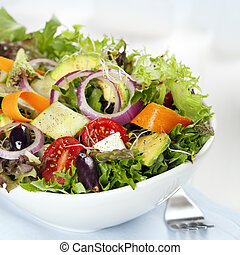 Salad in white bowl. Mixed greens with black olives, tomatoes, and lots of vegetables.