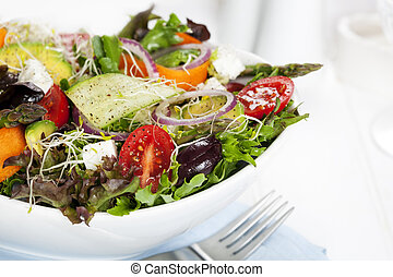 Salad in white bowl. Mixed greens with black olives, ...