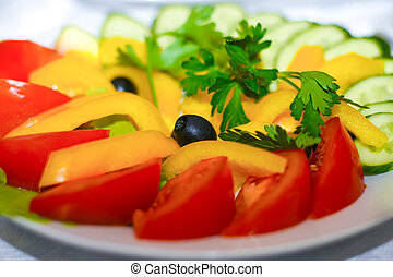 Salad of assorted vegetables in a plate stands on a festive table. Red tomatoes, cucumbers, olives, yellow pepper, parsley