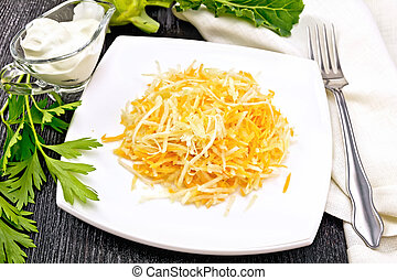 Salad of carrot and kohlrabi in white plate on board