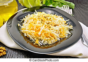 Salad of carrot and kohlrabi with honey in plate on black board