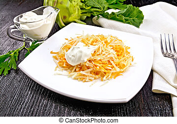Salad of carrot and kohlrabi with sour cream in plate on black b