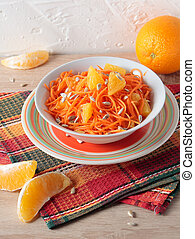 Salad of carrots with orange slices and sunflower seeds